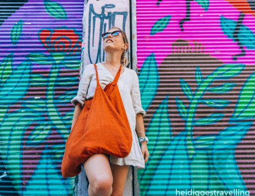 Young blond woman leaning against a concrete pillar separating two street art painted walls