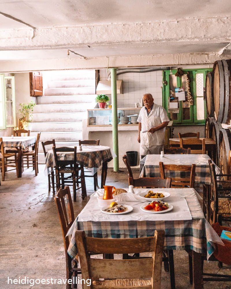Picture of the interior of a traditional Greek taverna and its white-haired owner