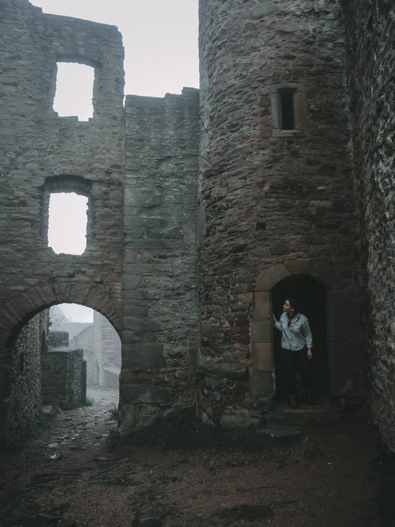 Young woman standing on the porch of a ruined castle