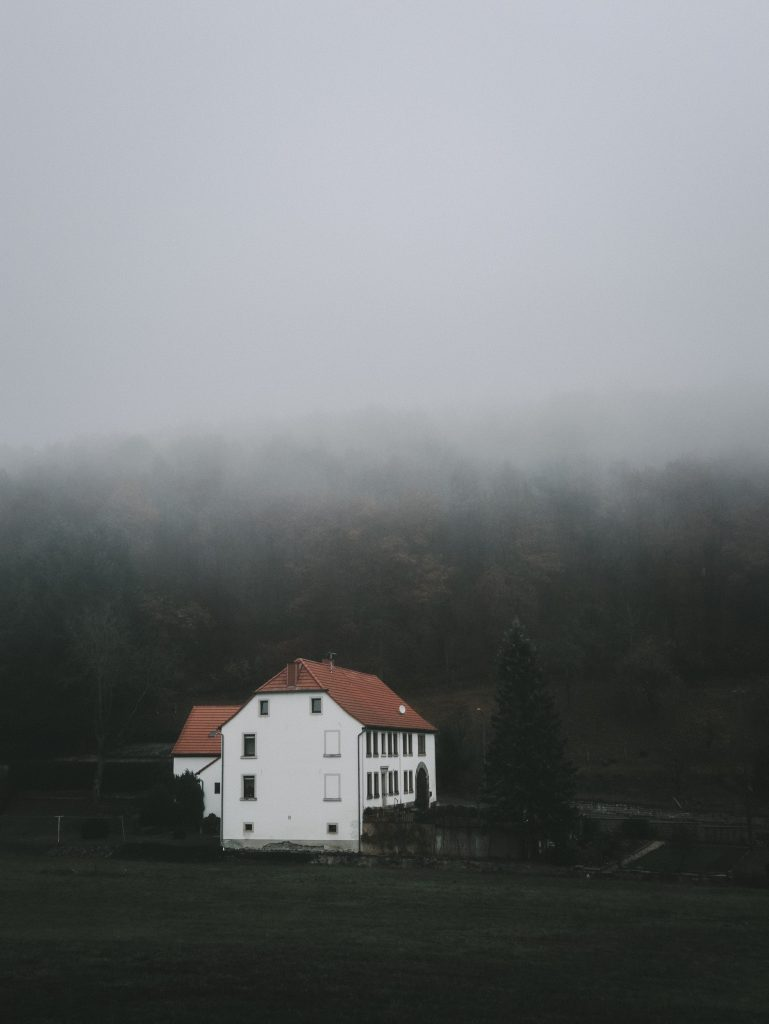 Picture of a big white house in the middle of a forrest and surrounded by misty clouds