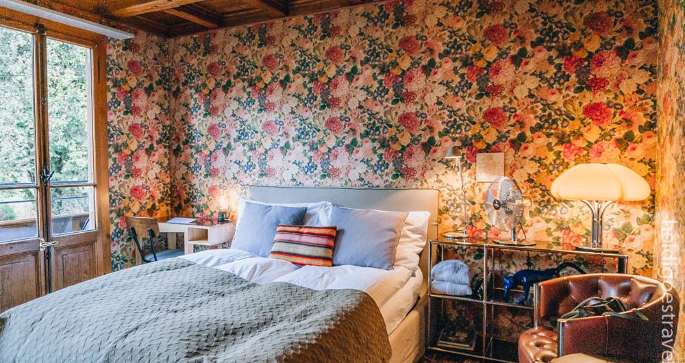 Picture of a bedroom lined with a bright flowery wallpaper