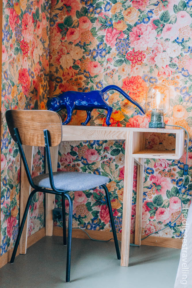 Picture of a small wooden desk and blue metal and wood chair leaned against a bright flowery wallpaper