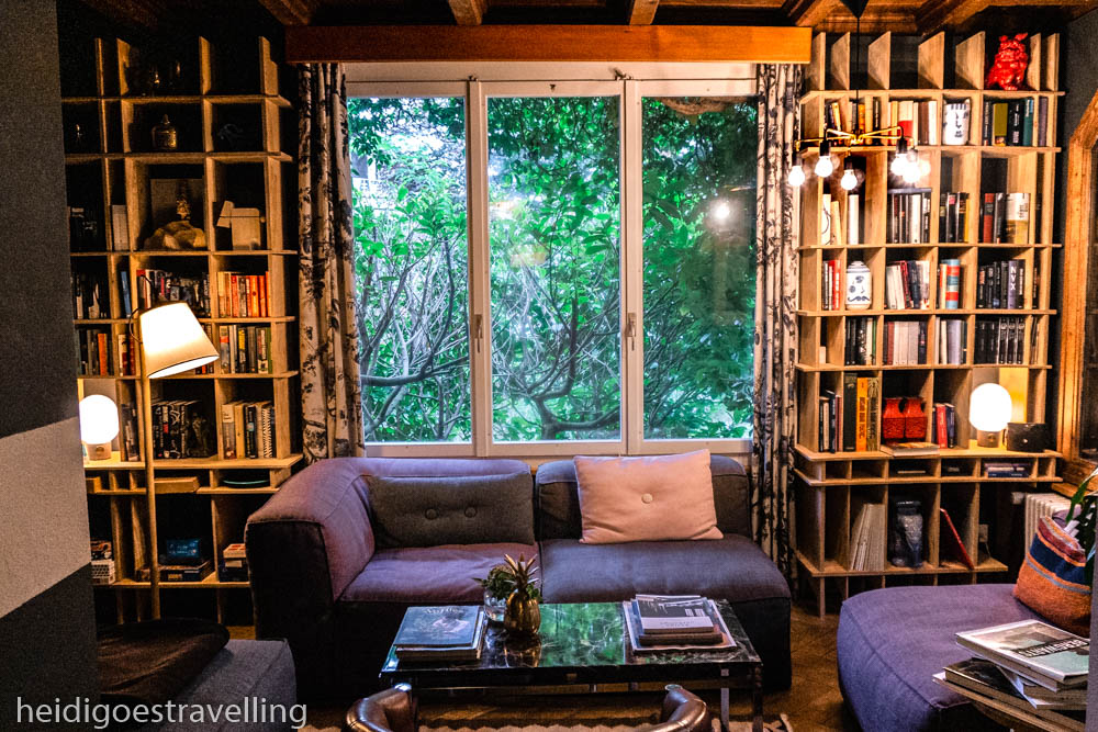 Picture of a cosy library with violet/grey sofas and a large window looking on lush green trees