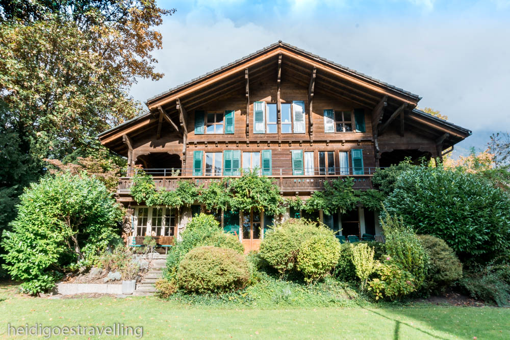 Picture of a large chalet with green shutters and in a lush garden