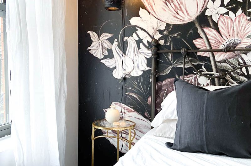 Picture of a bedroom with a bold black, white and blush wallpaper behind a bed covered with charcoal, blush pink and white linens