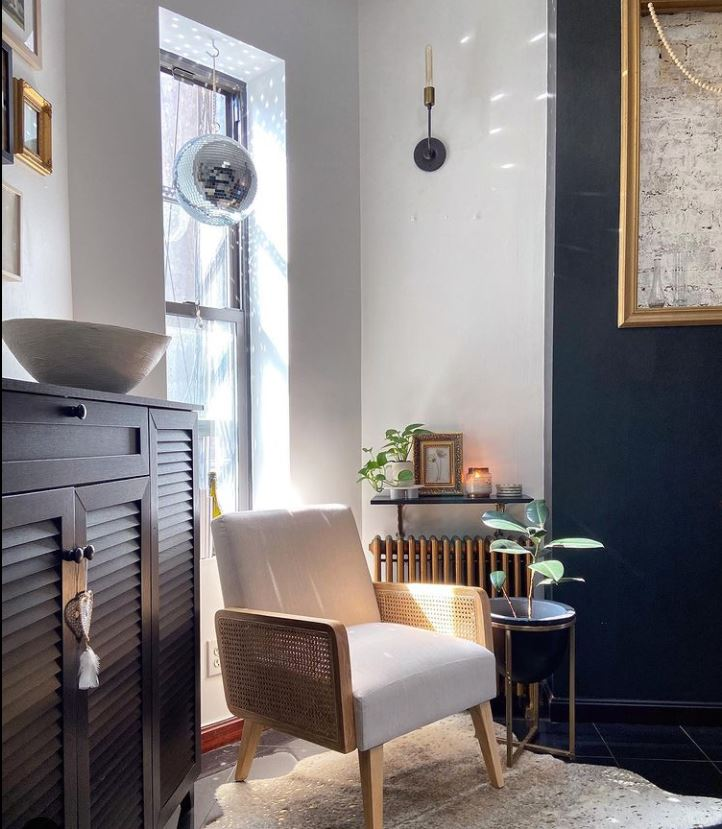 Picture of tiny lounge area with a white and rattan chair and white and charcoal grey walls